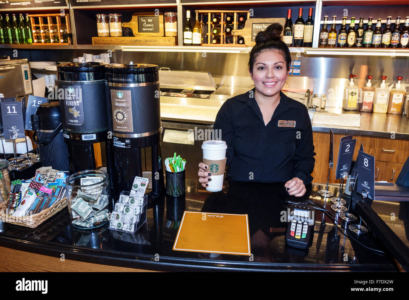 Stuart Florida Courtyard by Marriott motel hotel lobby cafe restaurant Starbucks Coffee Hispanic woman barista employee - Stock Image