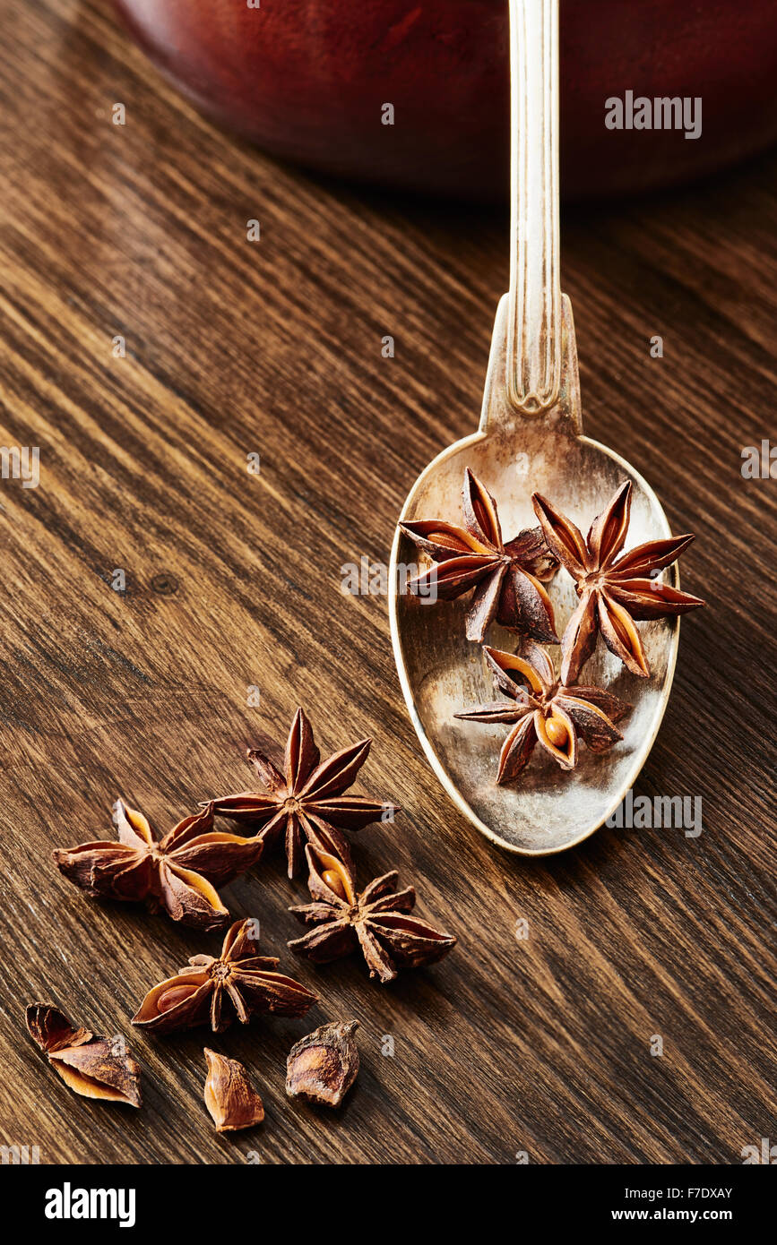 Star anise on old spoon surrounded by star anise on dark wood table - Stock Image