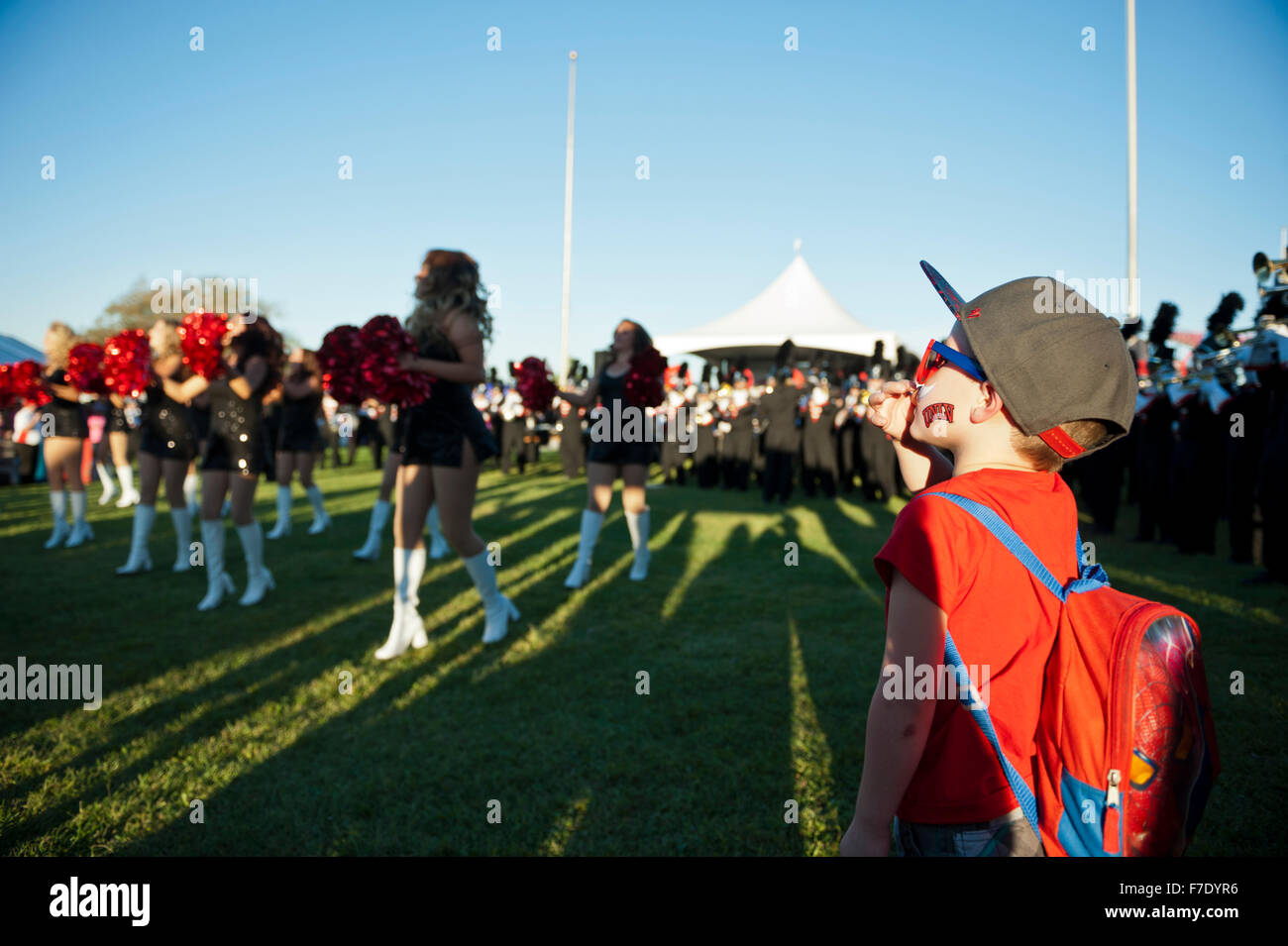 A young boy watching the UNLV (University of Las Vegas) Rebels Cheerleaders at a Rebels Football pre-game event - Stock Image