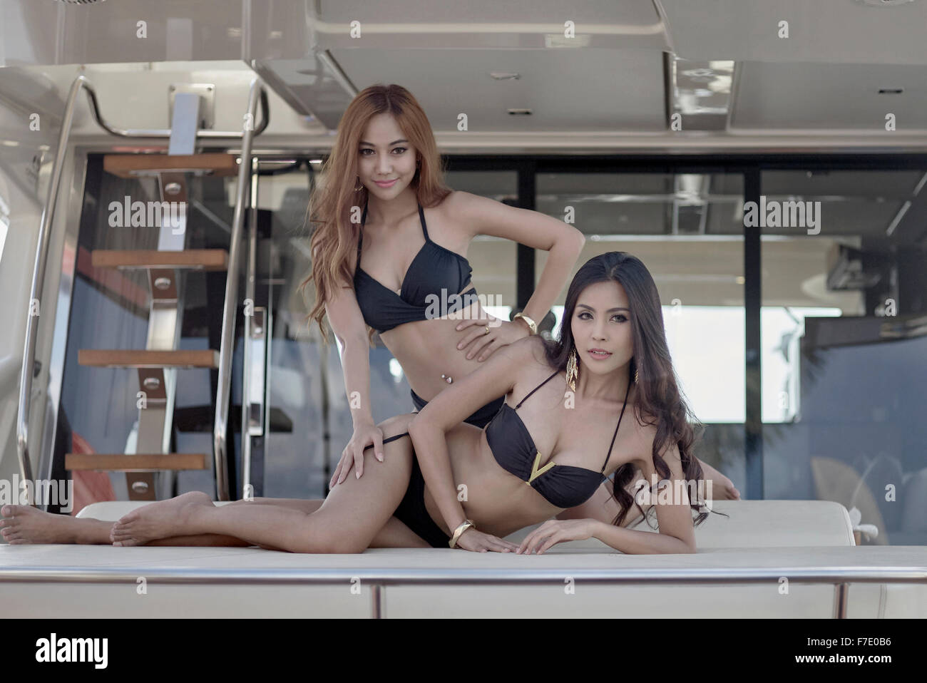 Promotion models in bikinis. Thailand boat show. S. E. Asia. - Stock Image