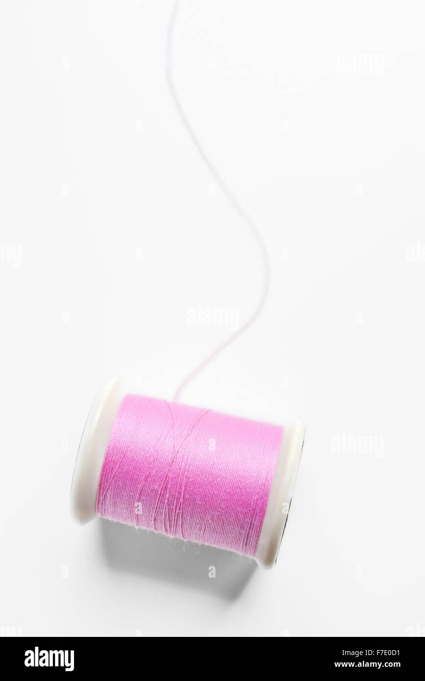 pink thread on white background - Stock Image