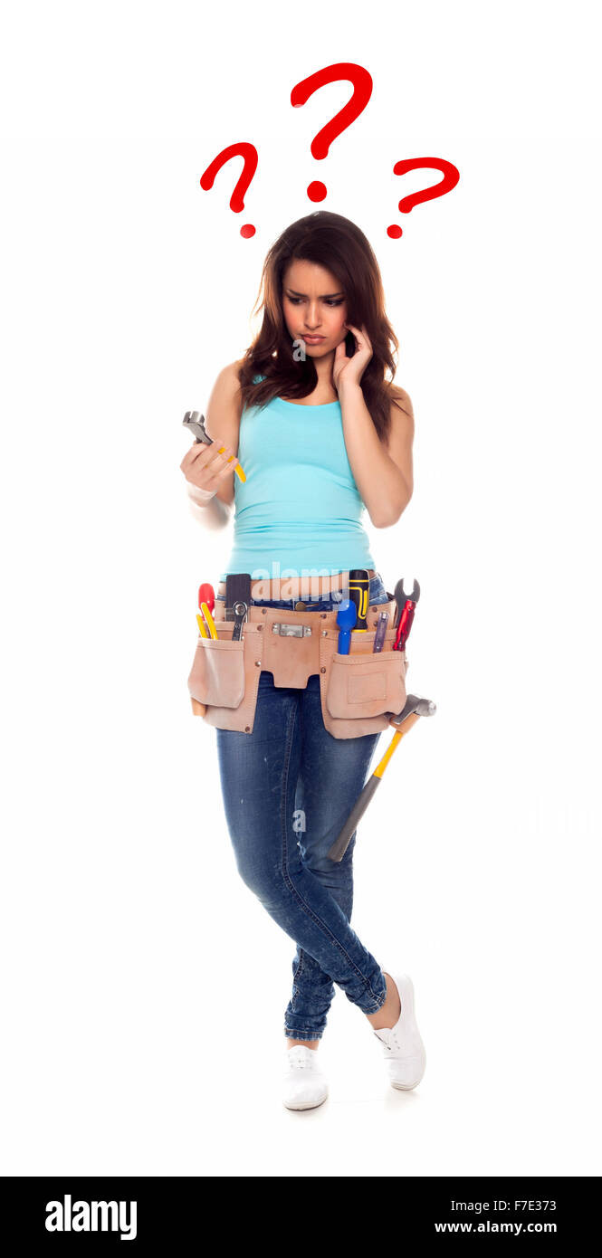 Confused woman with tools over a white background. - Stock Image