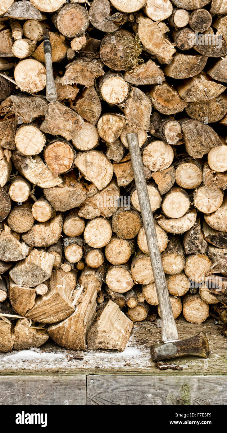 Full woodshed in winter with a splitting maul and hatchet. - Stock Image