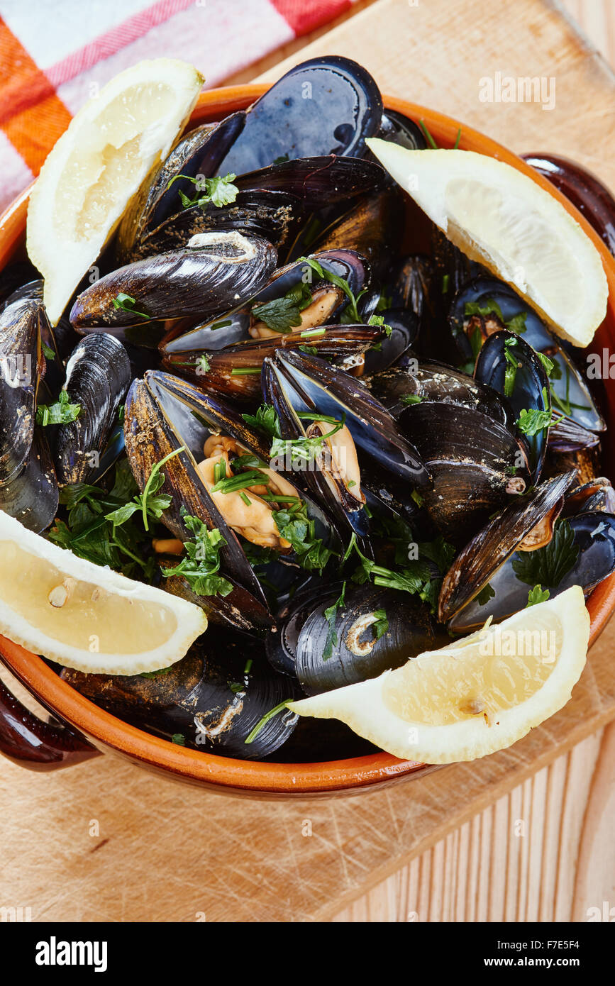 Mussels in a pot on the cutting board, lemons, tablecloth on wooden table - Stock Image