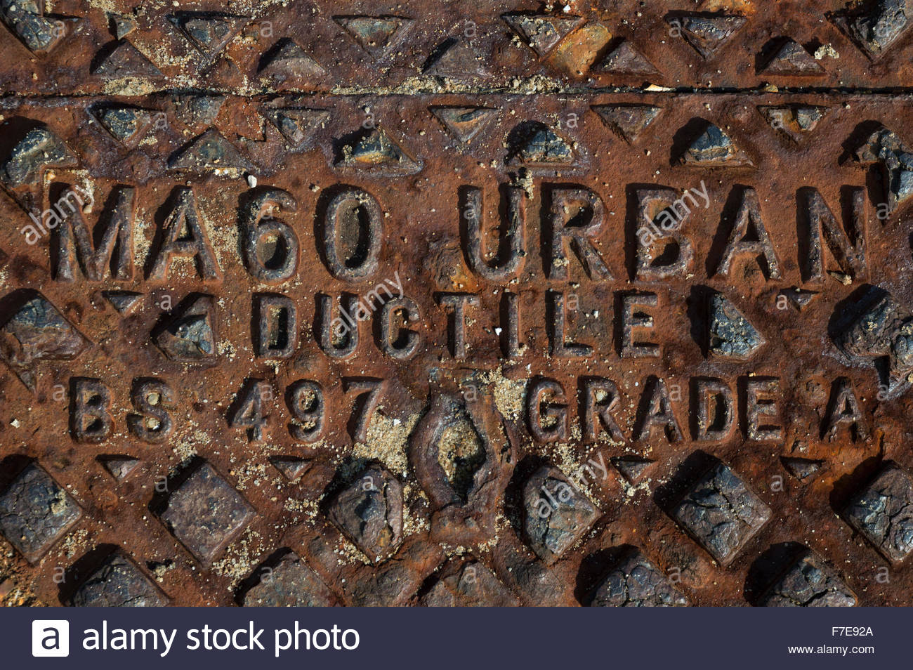 Close-up of a rusting MA60 Urban Ductile BS 497 Grade A manhole cover. - Stock Image