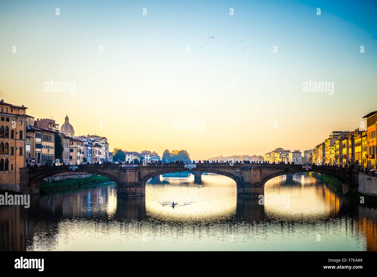 The amazing Ponte Vecchio over Arno River in Florence, Italy. Under the bridge one guy rowing - Stock Image
