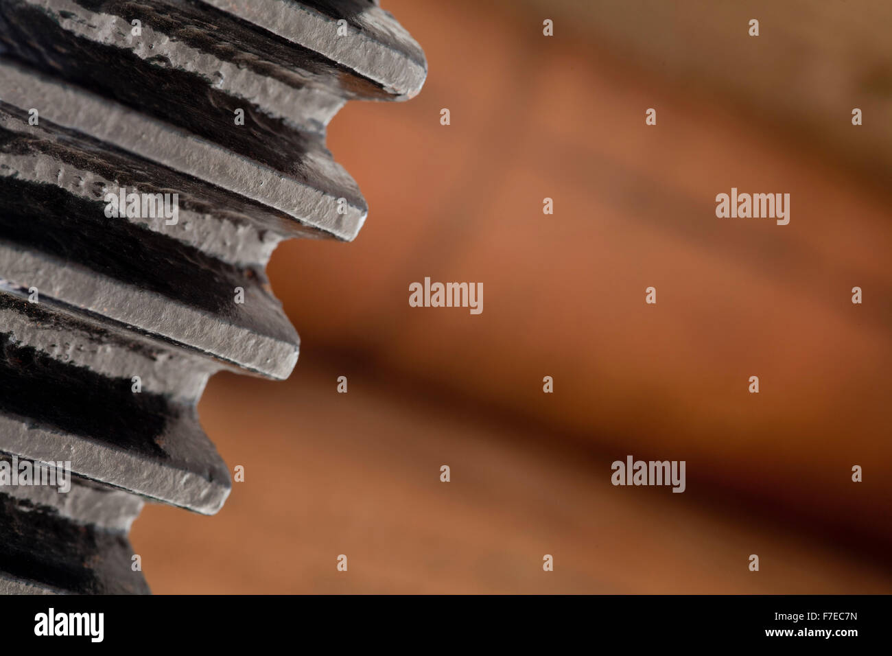 black cog on brown background or close-up of machine part - Stock Image