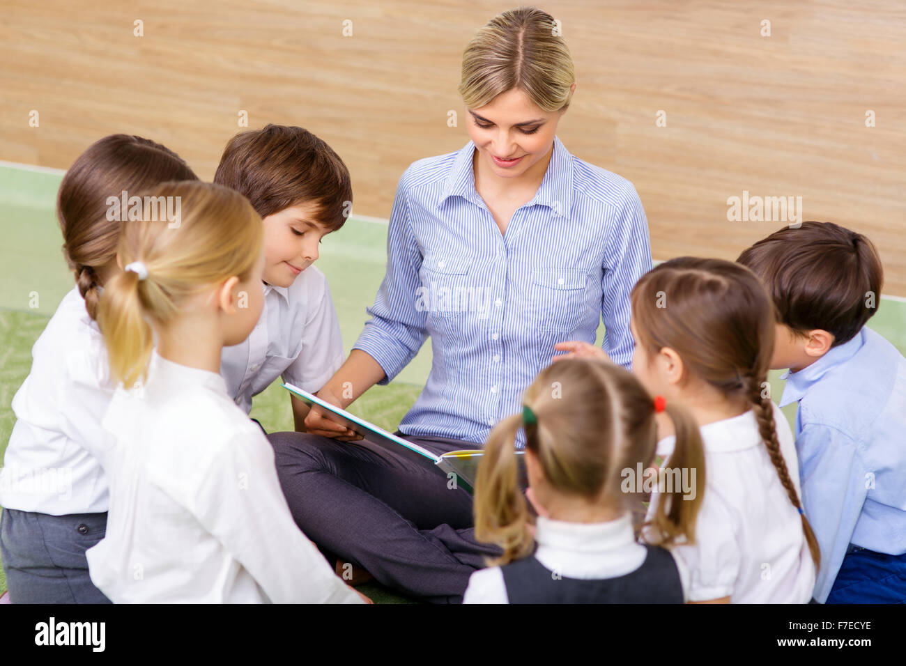 Kids and their teacher at reading session. - Stock Image