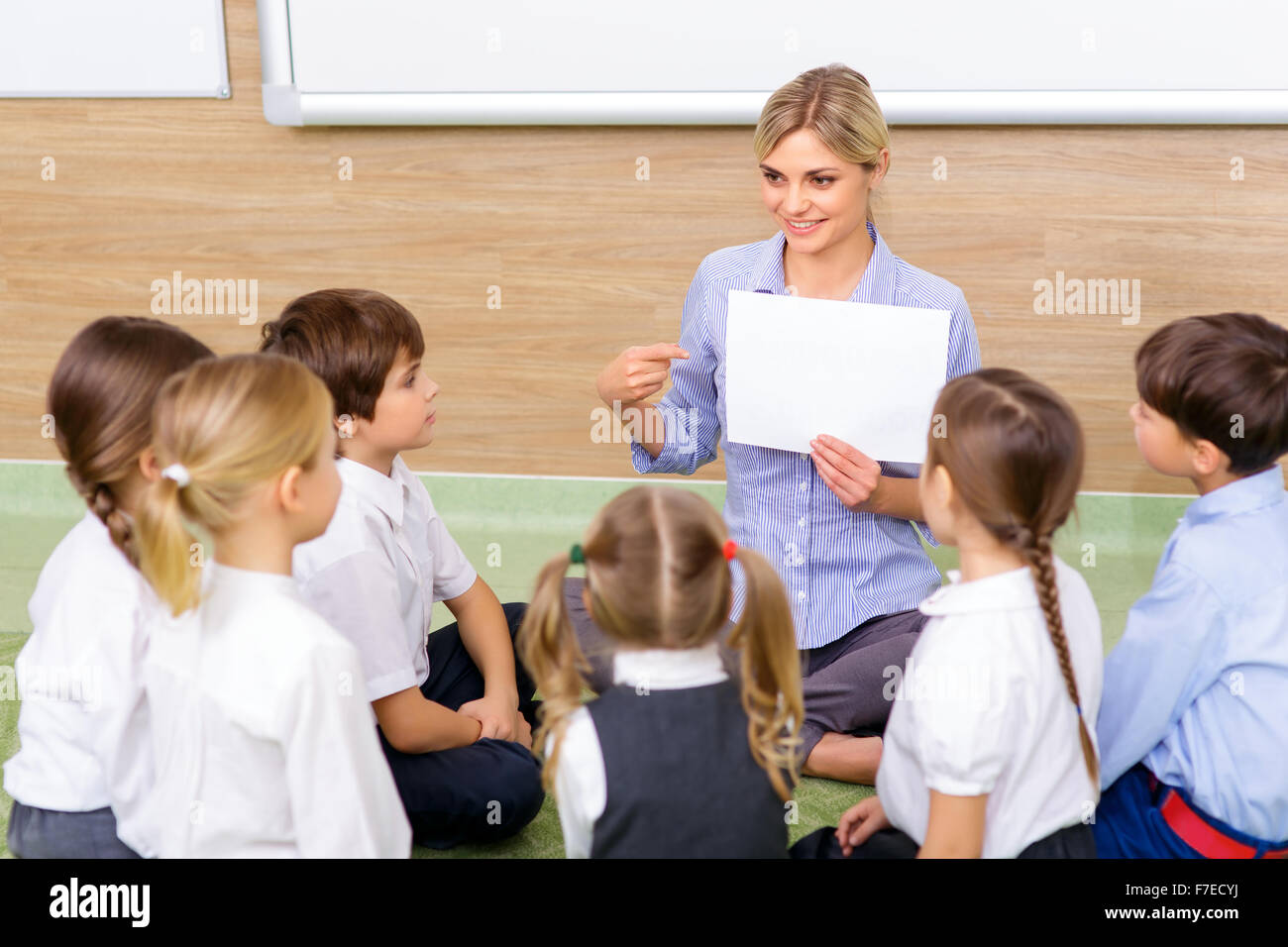 Teacher and kids are sitting in circle together. - Stock Image