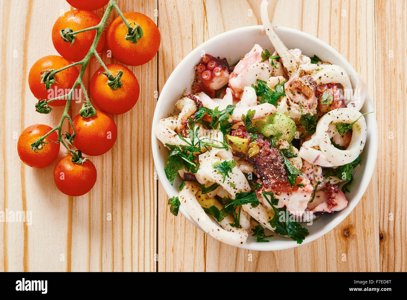Seafood salad in white bowl, tomato, on light wooden table - Stock Image