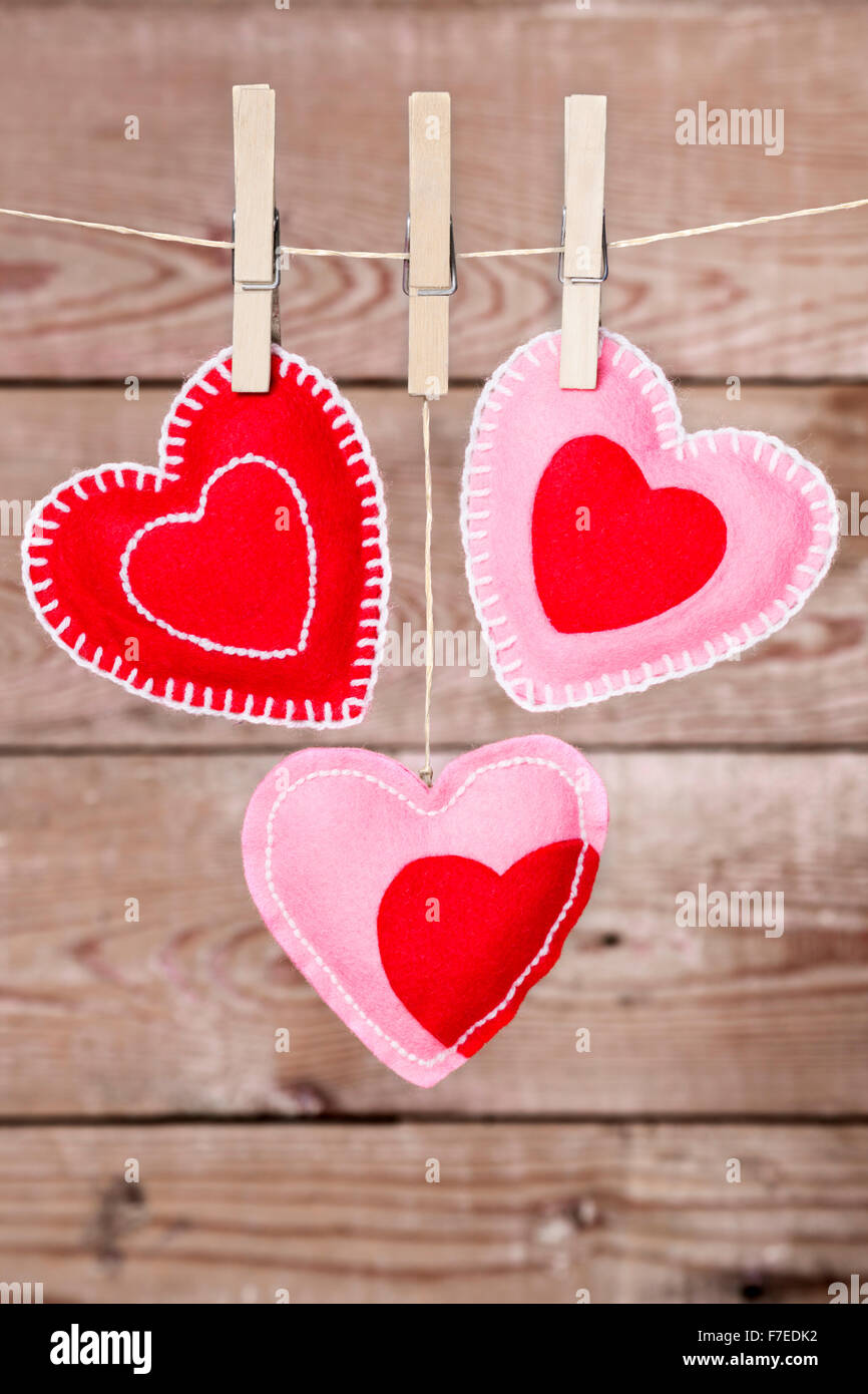 A clothesline with cute Valentine's Day hearts decorations on a rustic background. - Stock Image