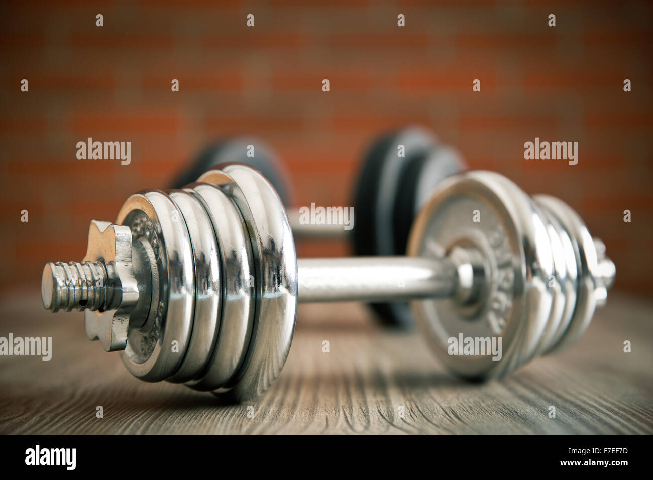 the iron dumbbell on wooden floor - Stock Image
