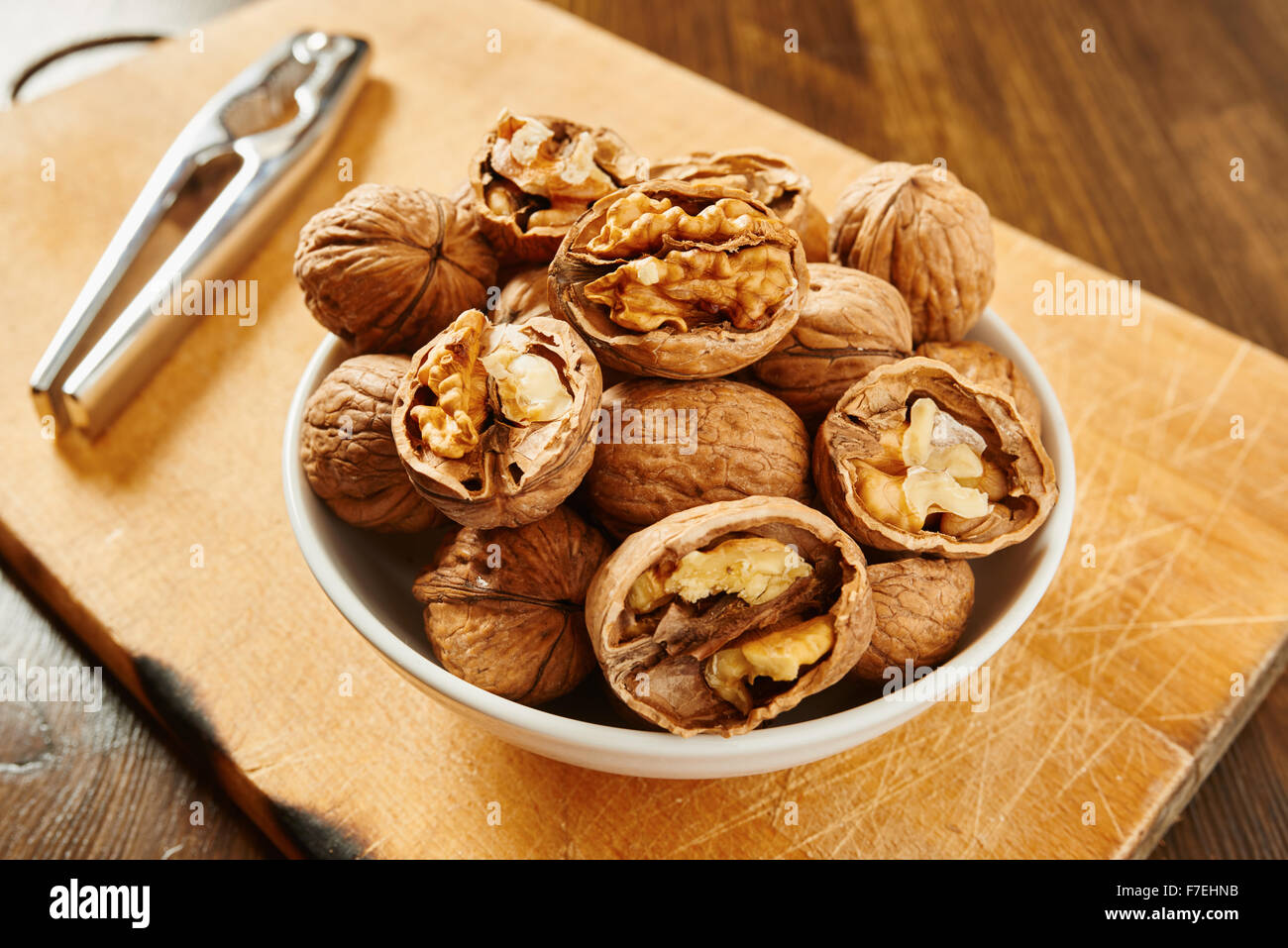 Walnuts on white bowl resting on a cutting board and wooden table - Stock Image