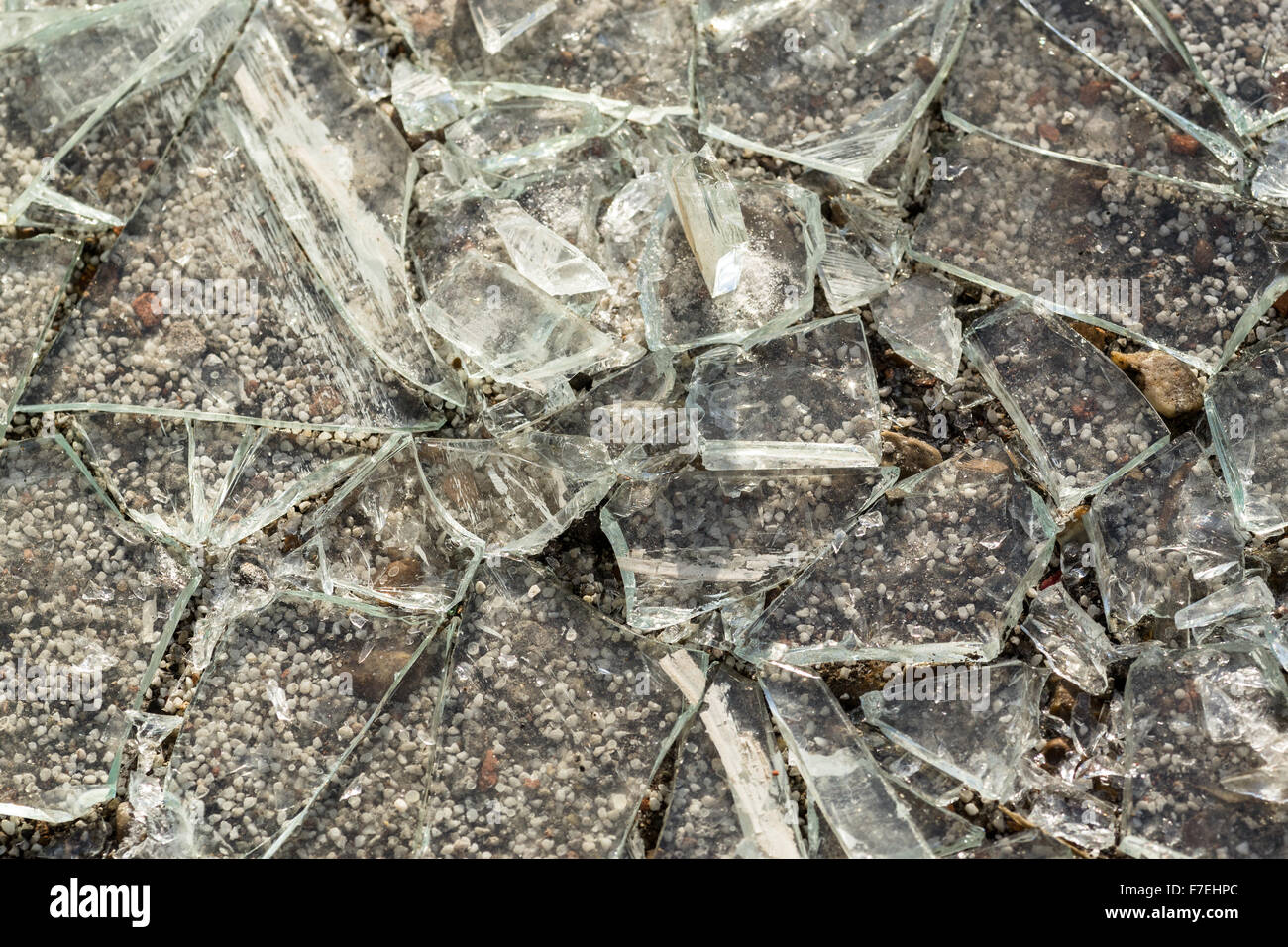 Macro shot of broken glass shards on a concrete pavement background - Stock Image