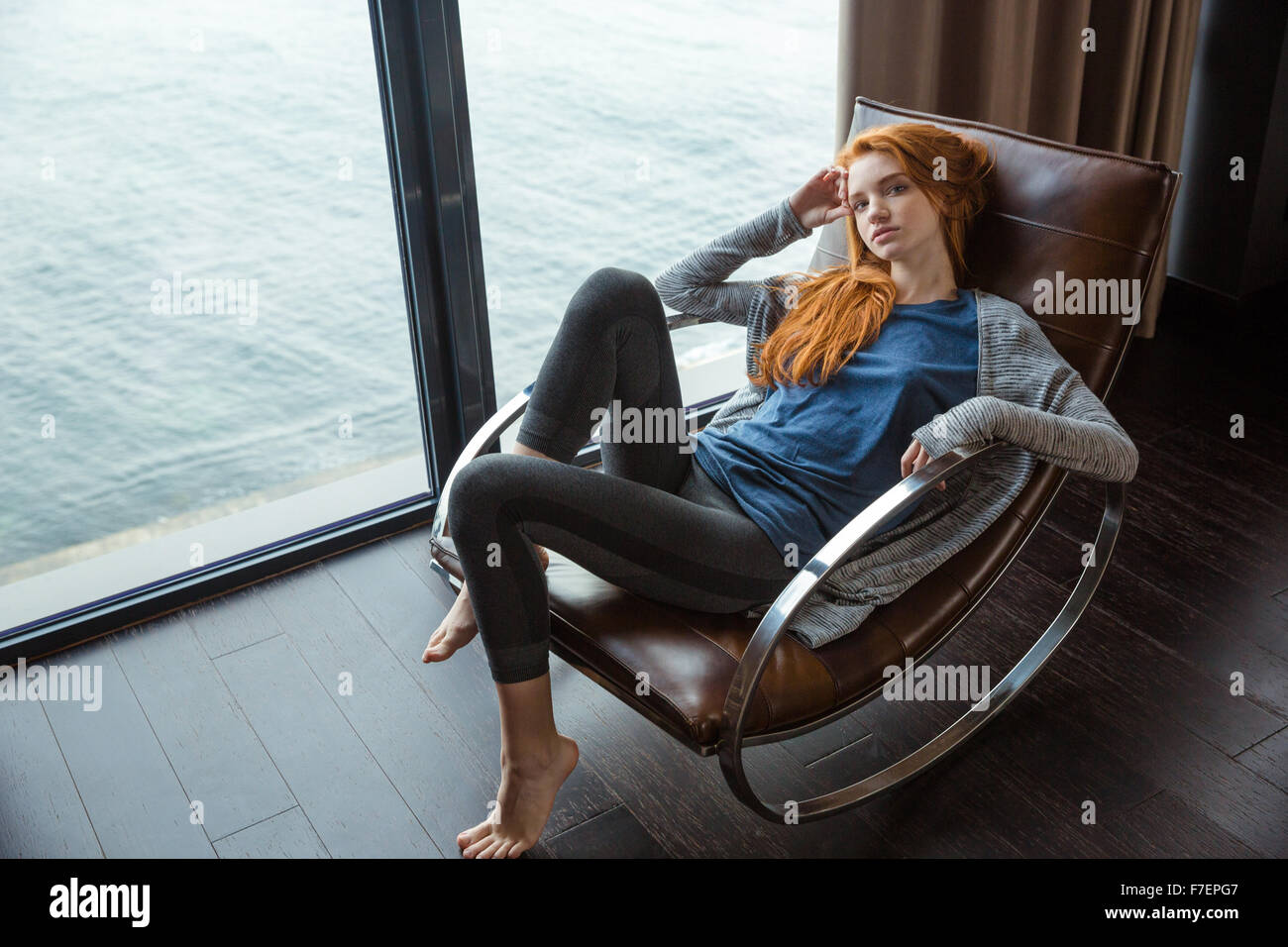 Portrait of a young redhead woman relaxing on rocking chair with sea view from the window Stock Photo