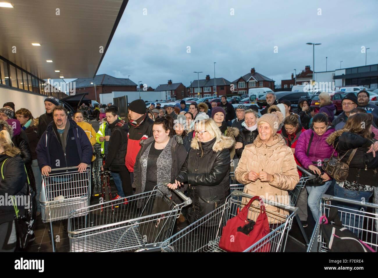 shoppers queue outside a supermarket - Stock Image