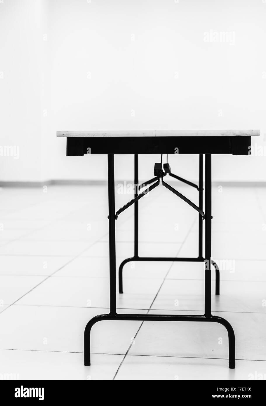Single solitary table in a white room creates a sense of cold starkness and clinical purity in this black and white - Stock Image