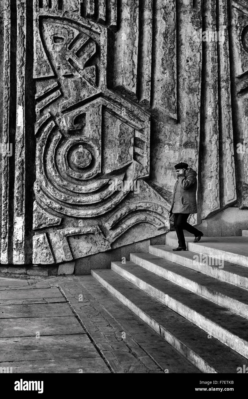 Classical diagonal stairs draw the eye towards a wonderful hand carved stone wall sculptures as an elderly woman Stock Photo