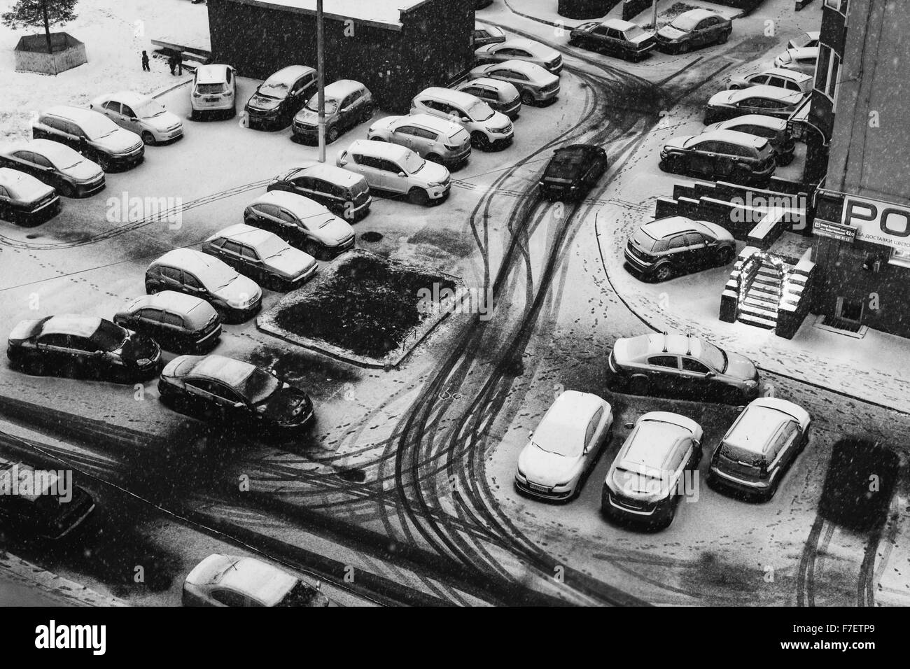 Many parked cars are parked as a snow storm starts to cover the vehicles in a contemporary street scene in Ufa, - Stock Image
