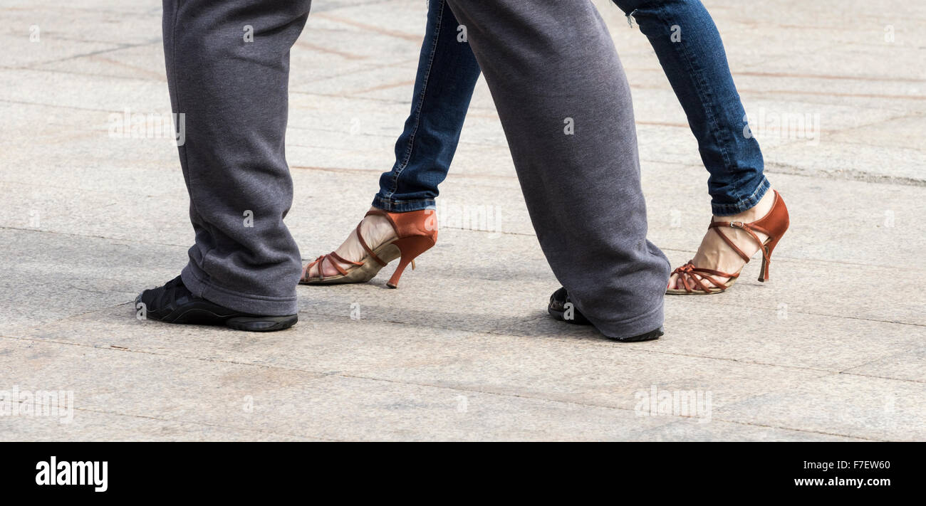 Couple dancing Tango at outdoor cafe in Spain. Woman wearing Jeans and heels; man wearing tracksuit and trainers. - Stock Image