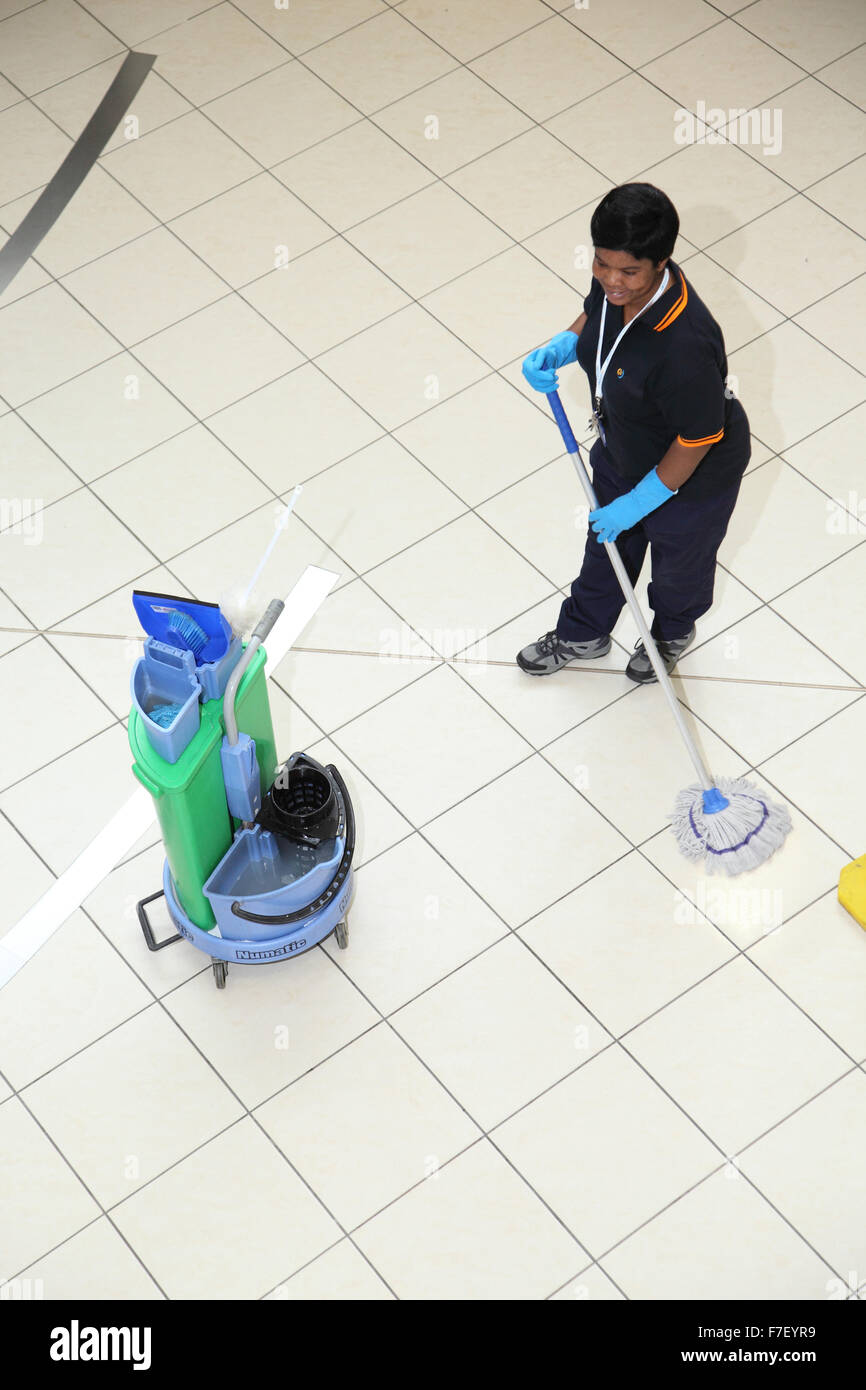 A hospital cleaner mops the floor in a modern UK hospital. Viewed from above. - Stock Image