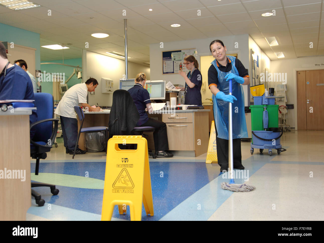 A hospital cleaner mops the floor in the ward administration area in a modern UK hospital. Wet floor sign in the - Stock Image