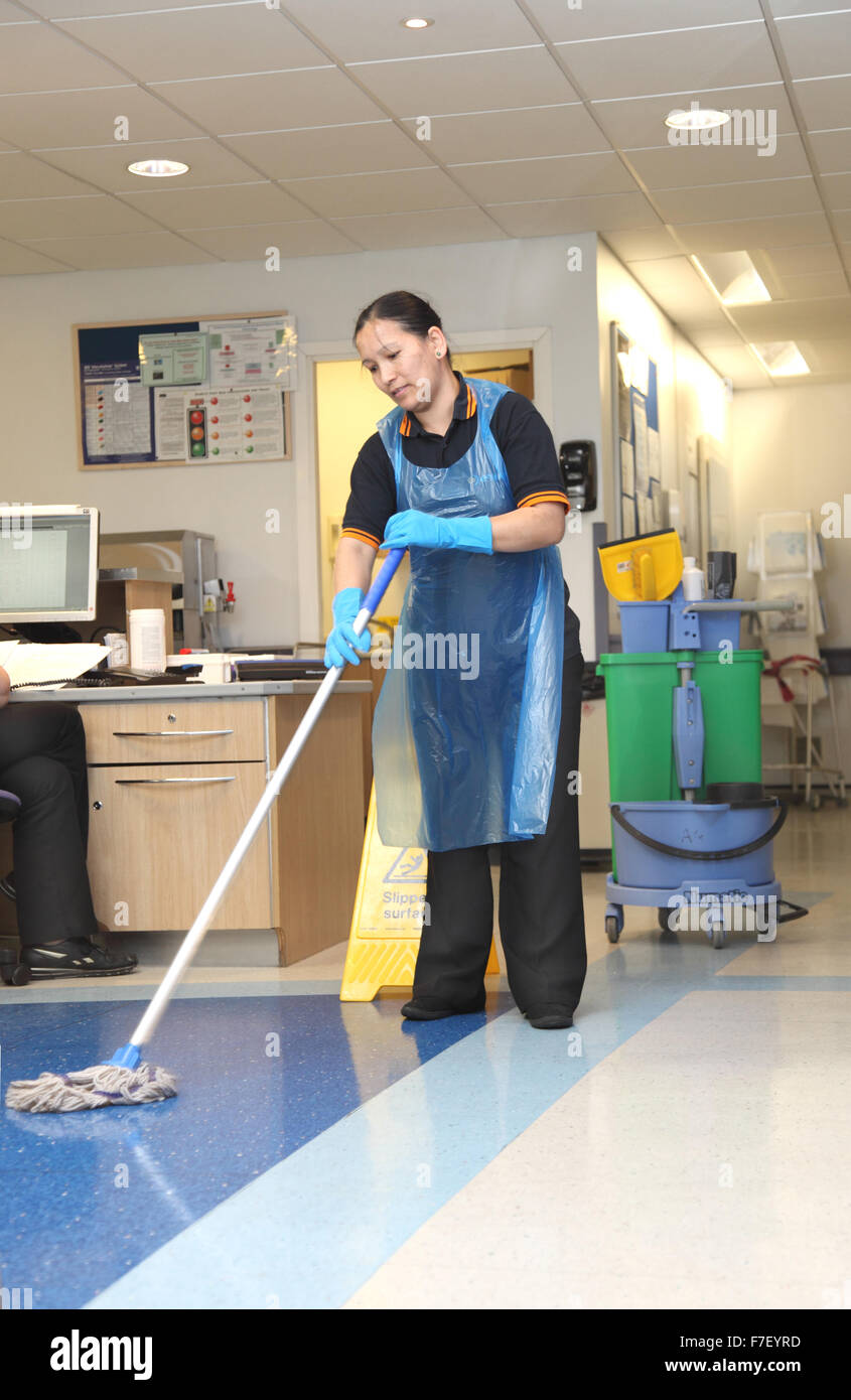 A hospital cleaner mops the floor in a ward in a modern UK hospital - Stock Image