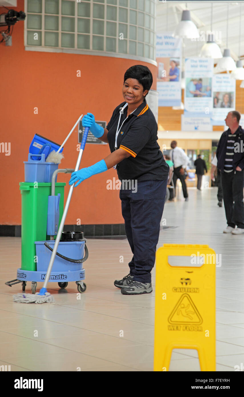 A hospital cleaner mops the floor in a modern UK hospital - Stock Image