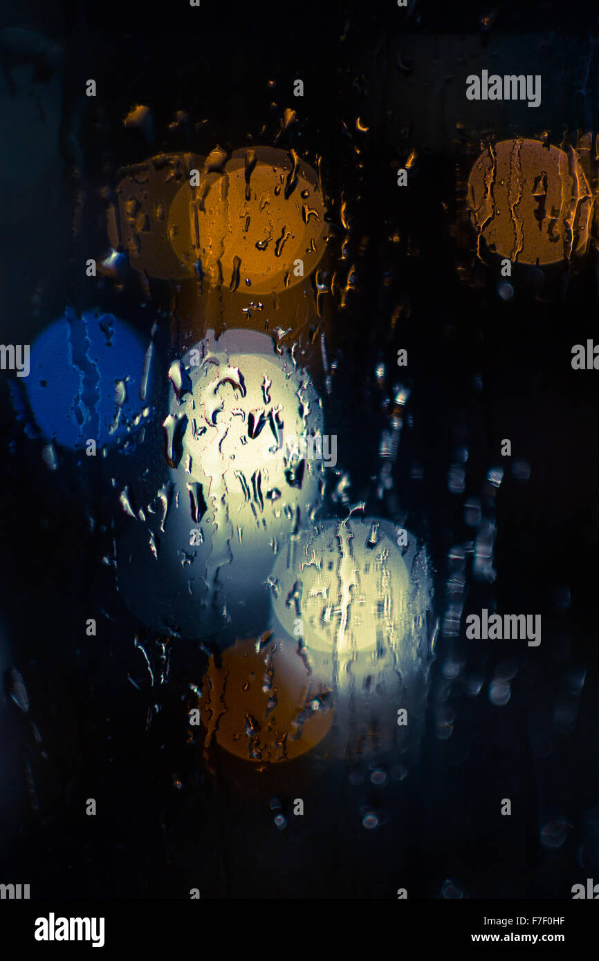 Car headlamps and street lights at night create bokeh style defocused blurs as rain water reflects off of windscreen Stock Photo