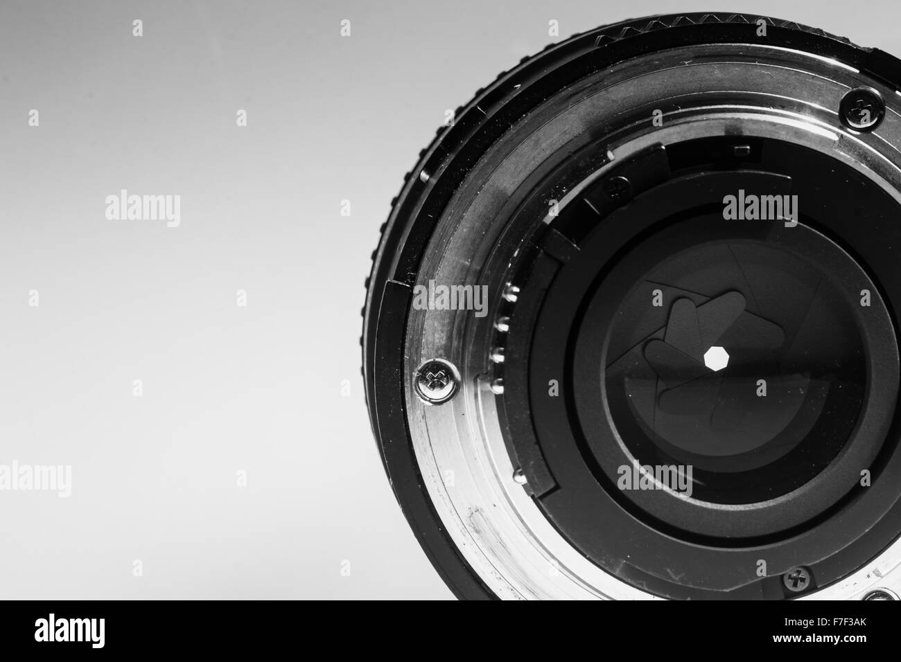 Close-up image of the rear end of a camera lens showing diaphragms and aperture rings in monochrome black and white - Stock Image