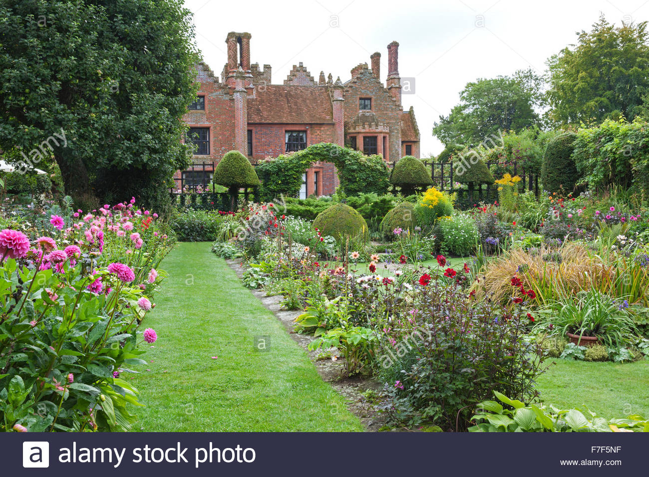 Chenies Manor Gardens - English Garden showing the House and summer Sunken Garden double borders with Dahlia and - Stock Image