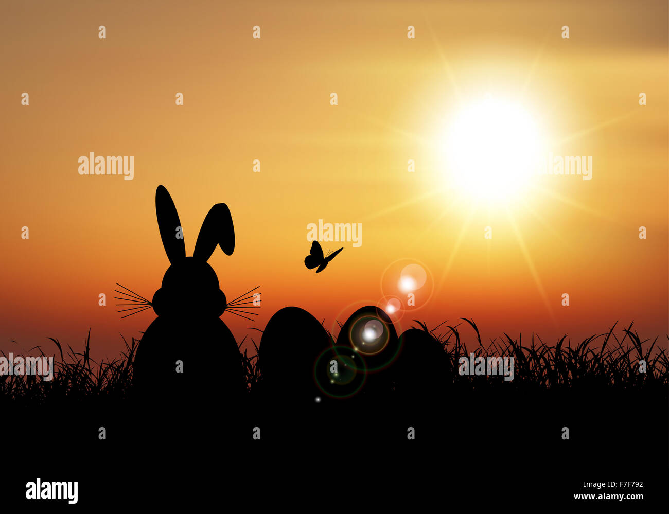 Silhouette of the Easter bunny sat in the grass against a sunset sky - Stock Image