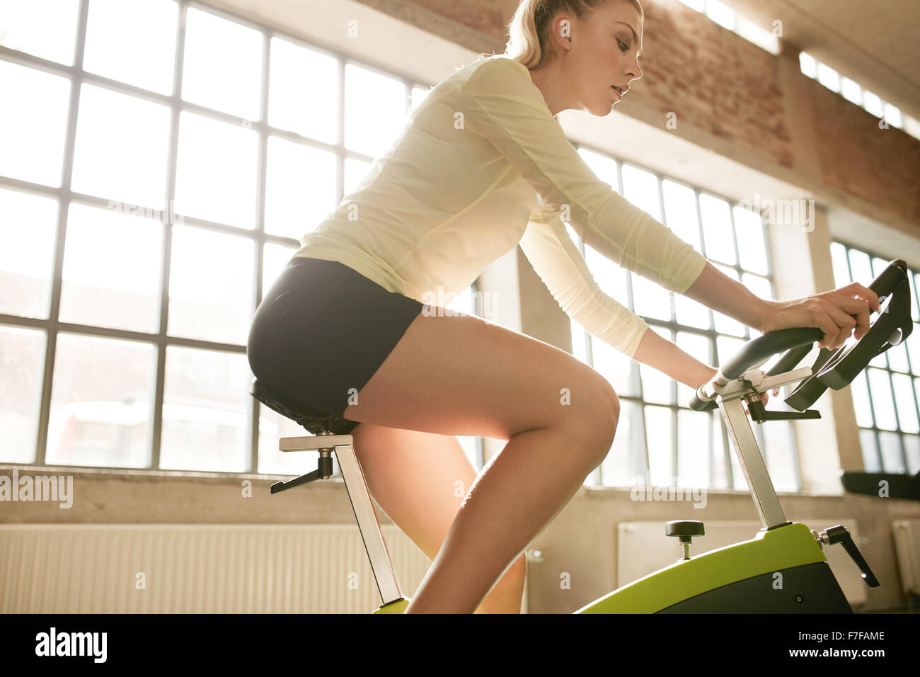 Side view of fitness woman on bicycle in gym. Young female athlete spinning on bicycles at health club. - Stock Image