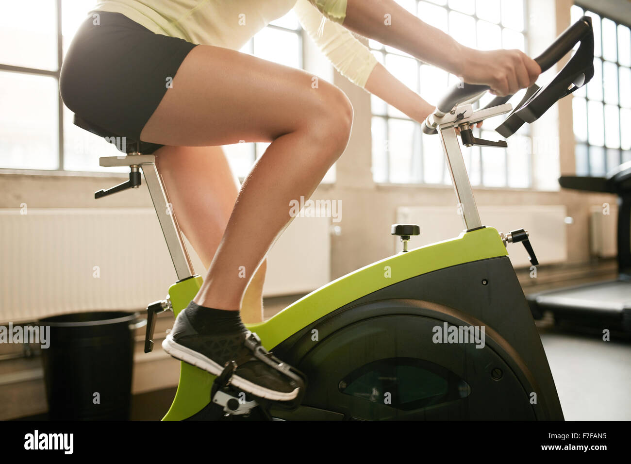 Cropped shot of fitness woman working out on exercise bike at the gym. Female exercising on bicycle in health club, - Stock Image
