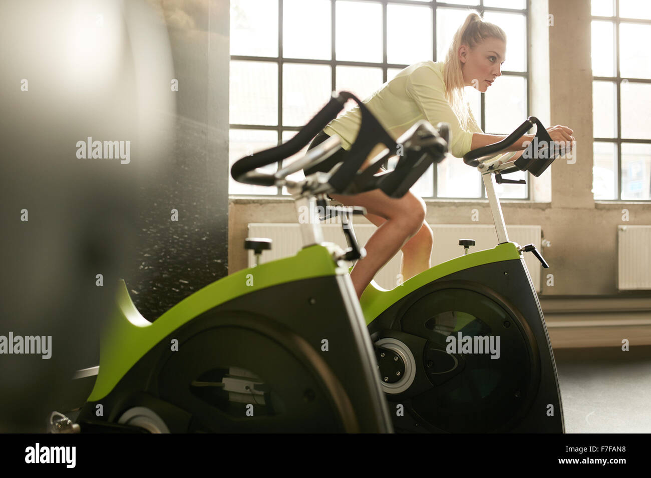 Fit woman working out on exercise bike at the gym. Indoor shot of a sportive woman doing fitness training on spinning - Stock Image