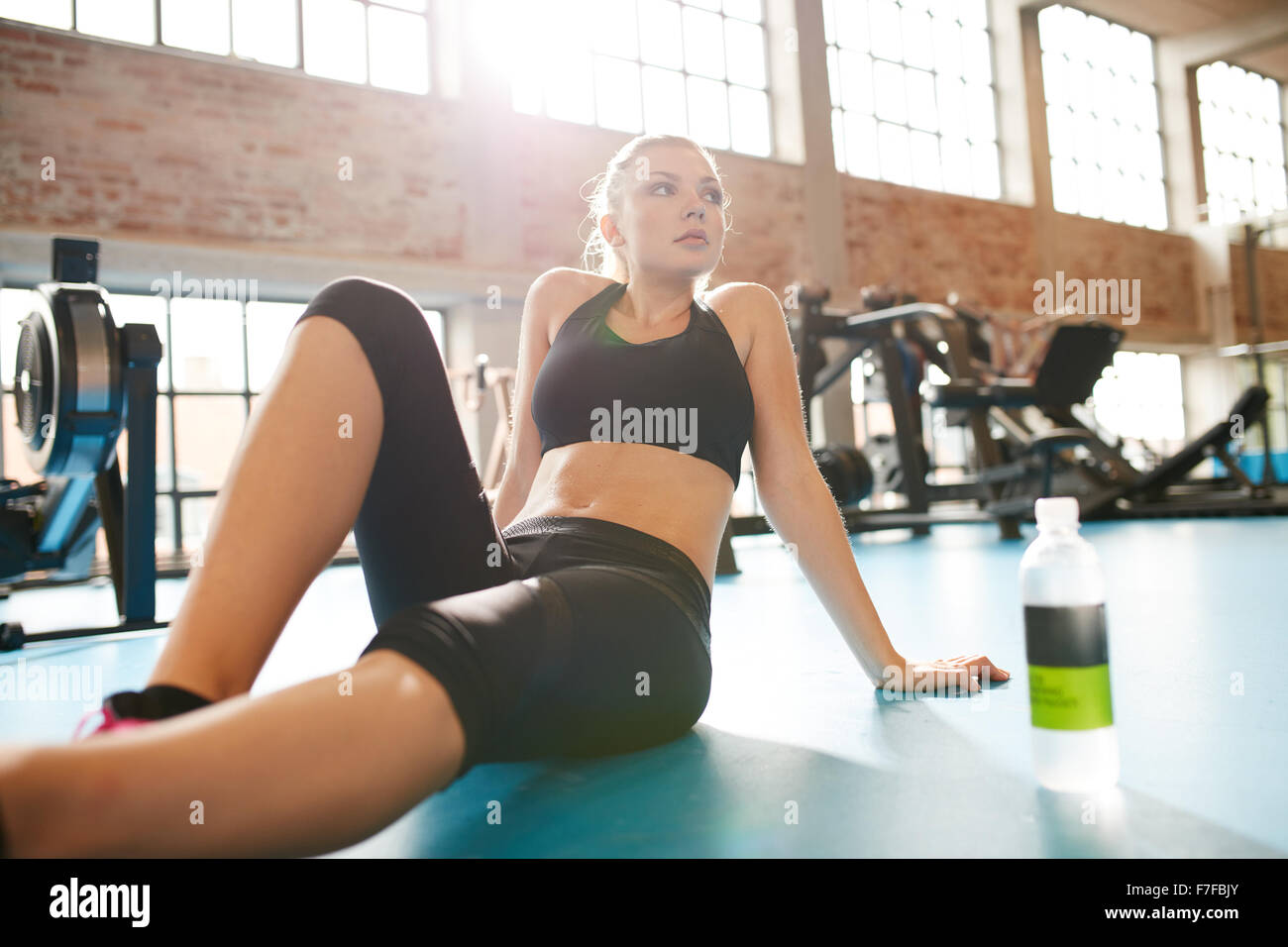 Portrait of a young woman during a break in the gym. Caucasian female sitting on floor looking away, resting after - Stock Image