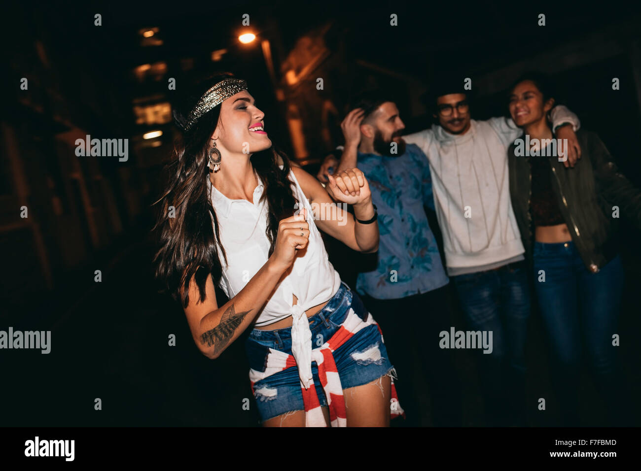Portrait of pretty young woman dancing with her friends in background. Happy young female enjoying in a party with - Stock Image