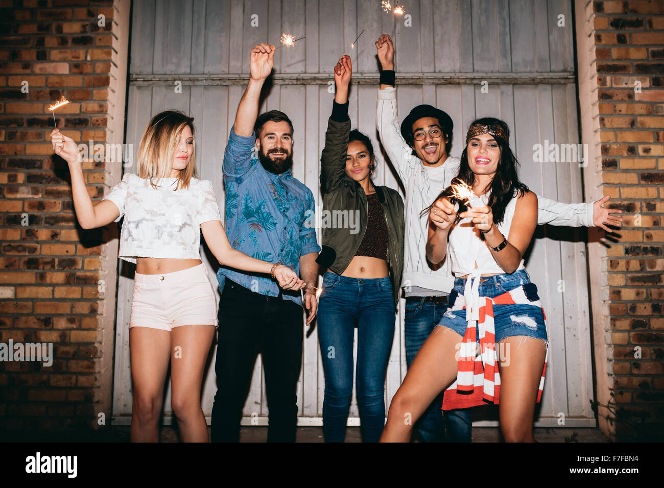 Happy young people out at night, celebrating with sparklers. Young friends having a party outdoors. - Stock Image