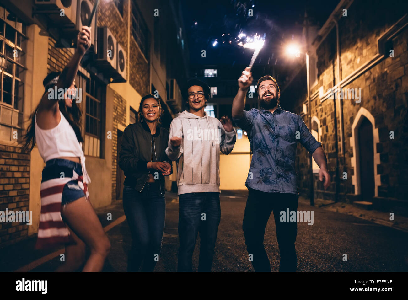 Shot of a young people playing with sparklers at night. Best friends hanging out at night and celebrating 4th of - Stock Image