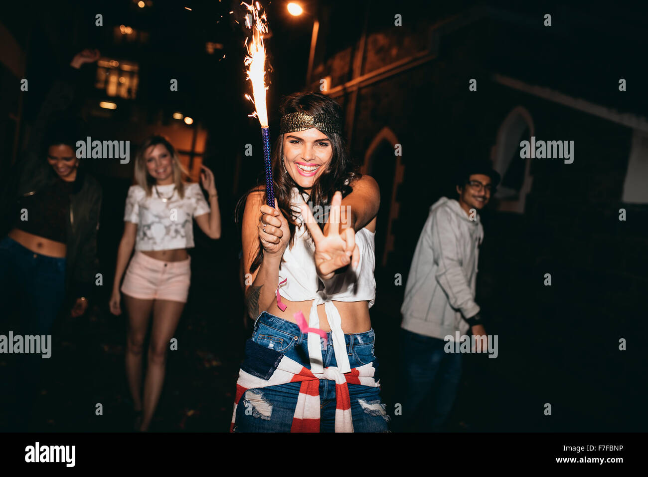 Portrait of cheerful young woman holding a sparkler and showing victory sign. Young people celebrating 4th of july - Stock Image