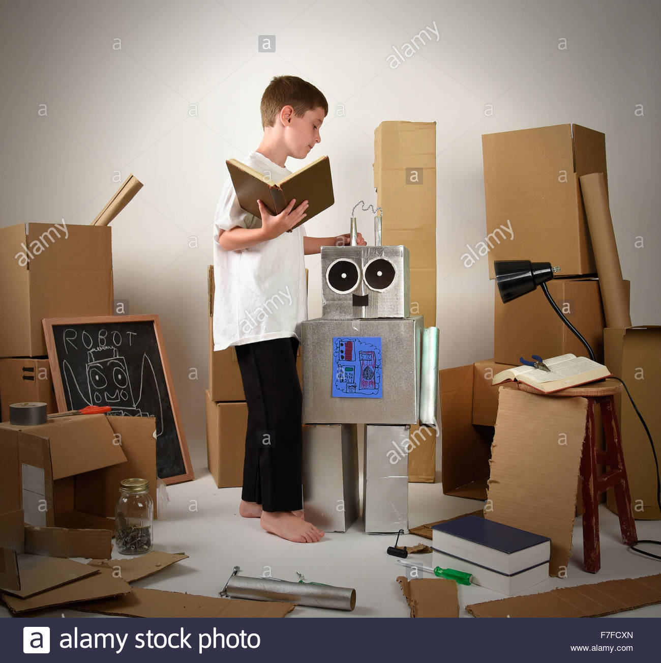A child is reading a book and building a robot from cardboard boxes for an imagination, science or education concept - Stock Image