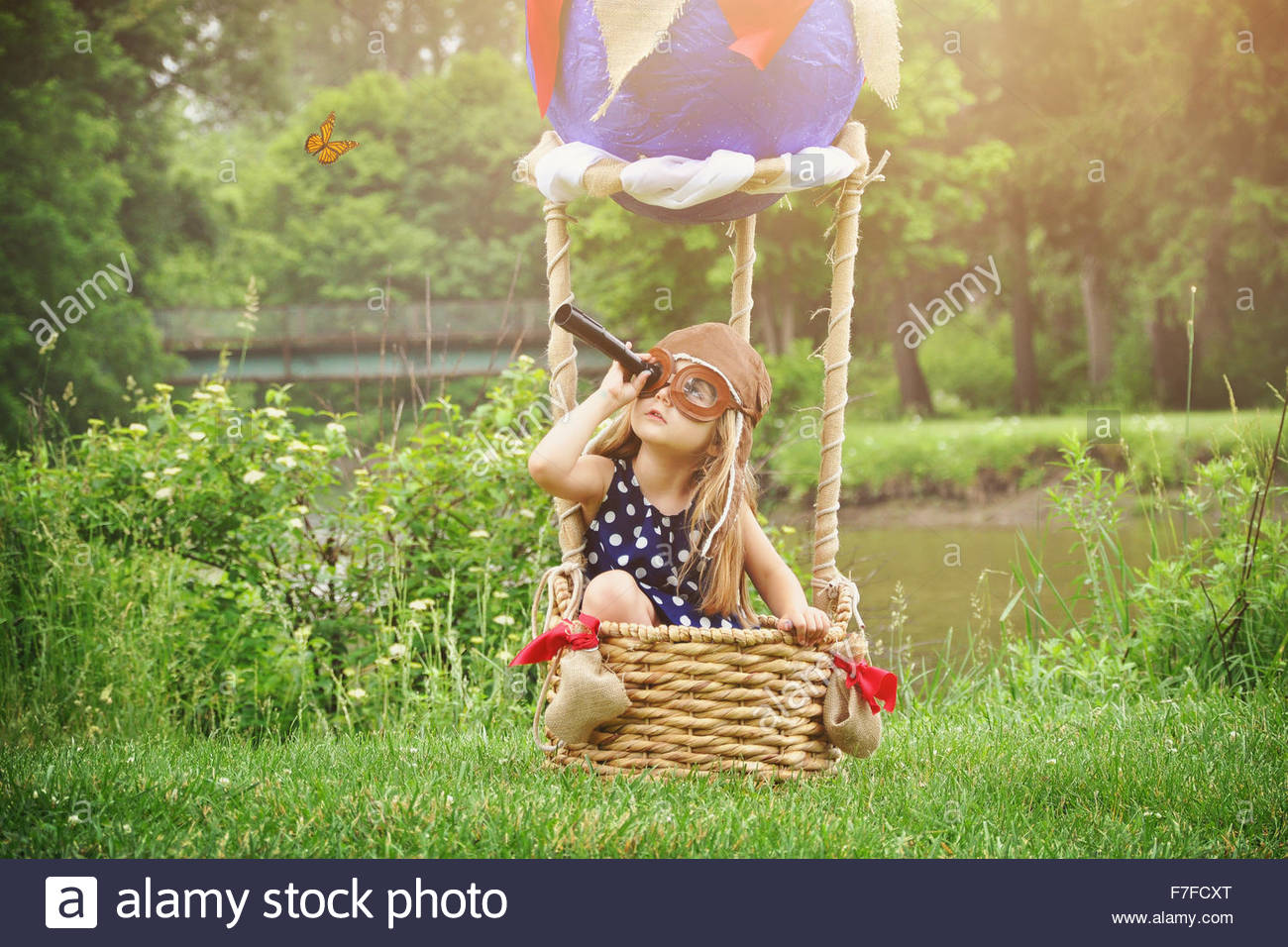 A little girl is sitting in a hot air balloon basket in the park pretending to travel and fly with a pilot hat on. - Stock Image