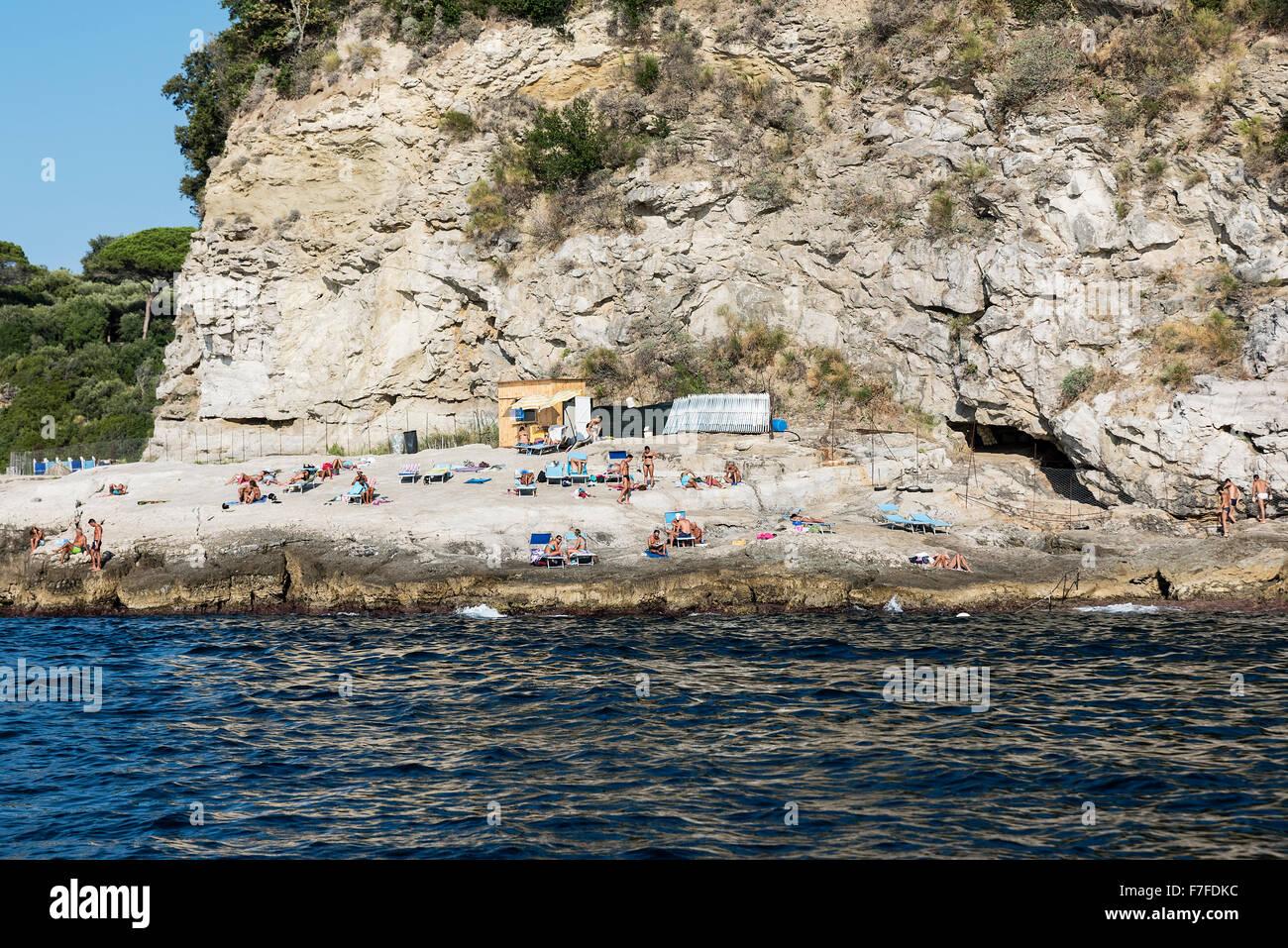 Sunbathers enjoy a rugged rock beach along the Sorrento coast, Compania, Italy - Stock Image