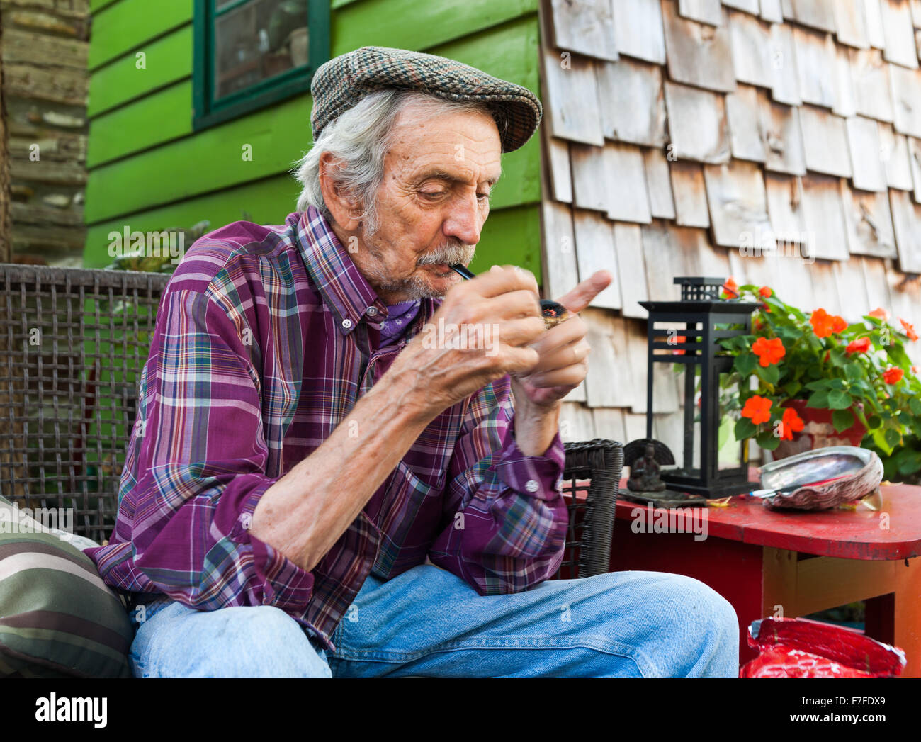 Lowell Davis lights up his corn cob pipe sitting outside his home at Red Oak II farm Carrthage, Missouri American - Stock Image