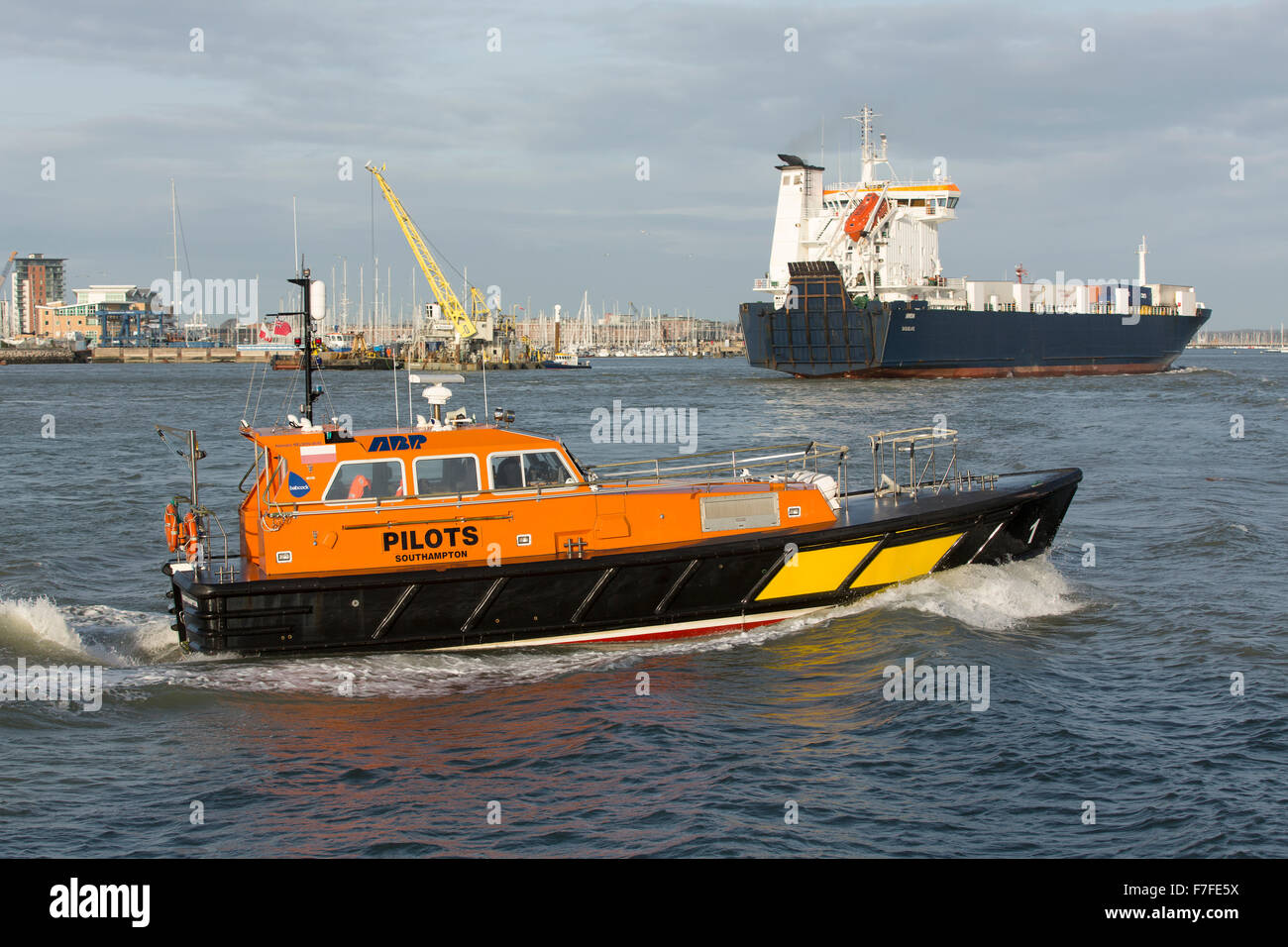 Orange and Black pilot boat crossing Portsmouth harbour at speed with a RoRo ferry loaded with containers in the - Stock Image