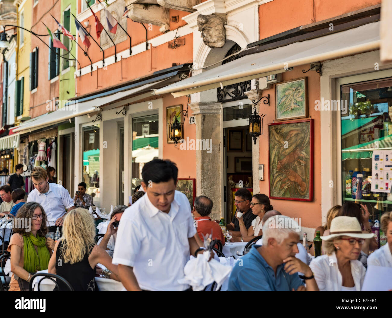 Patrons at an outdoor cafe restaurant, Burano, Venice, Italy - Stock Image