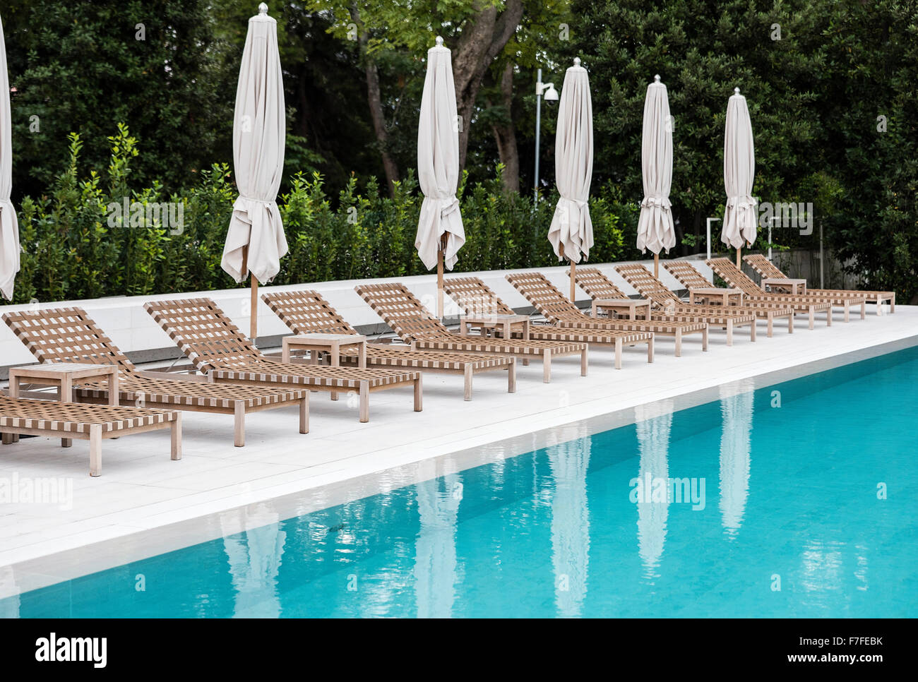 Poolside lounge chairs at an upscale pool. - Stock Image