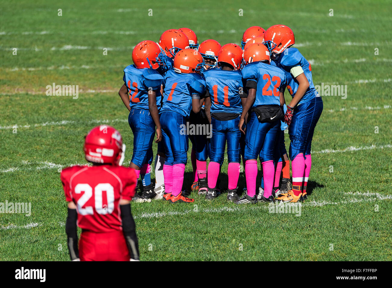 Young boys in the huddle during a Pop Warner football game, USA - Stock Image