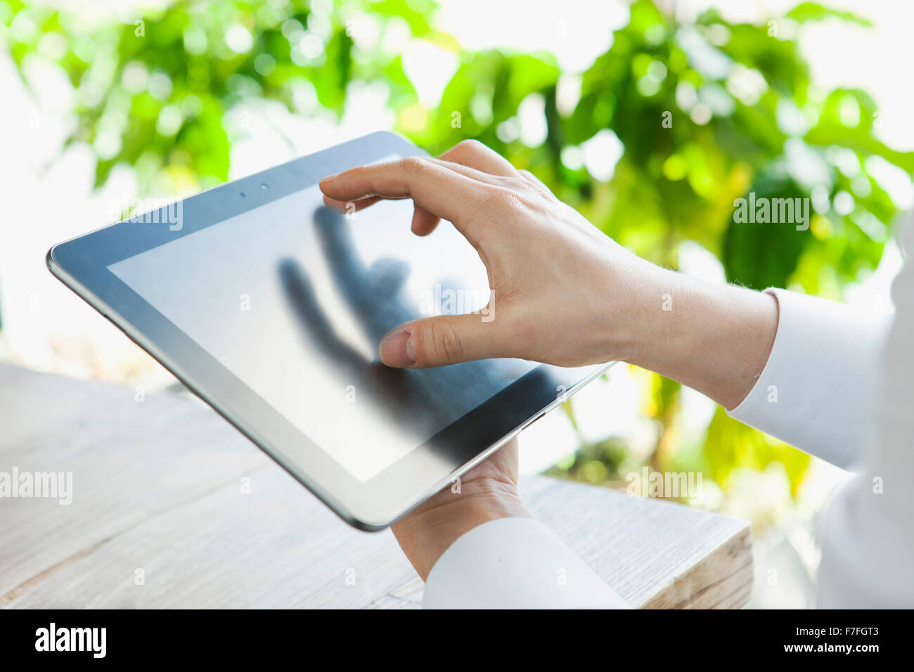 a man tapping a table PC - Stock Image