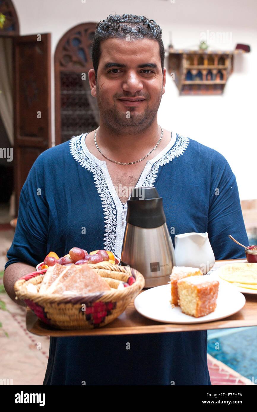 Waiter serving breakfast at Riad El Zohar, Marrakech, Morocco. - Stock Image